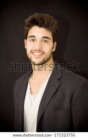 Fashion young man with jacket over black background - stock photo