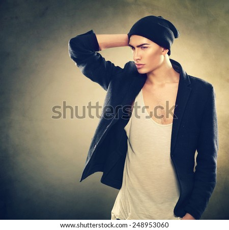 Fashion young model man portrait. Handsome Guy wearing hat. Vogue style image of stylish young man. Studio fashion portrait. - stock photo