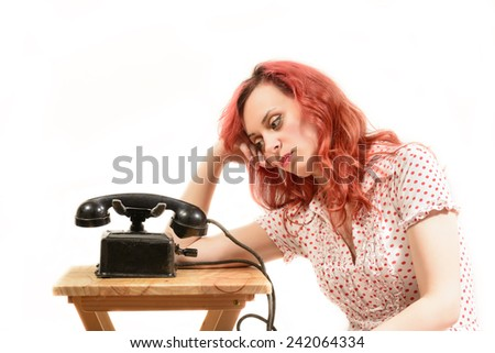 Fashion young redhead woman with a retro look waiting by the phone, isolated on white. Waiting for you're call! - stock photo