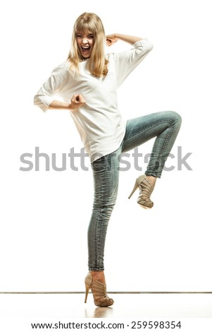 Fashion. Young woman denim pants white sleeve top high heels. Female model in full length celebrating success with arm raised isolated