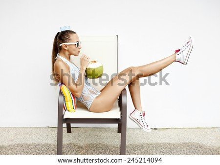 fashion young woman  drinking coconut water and sitting on chair . Outdoor lifestyle portrait - stock photo