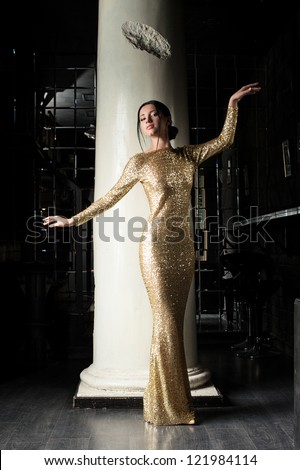 Fashion young woman in gold dress