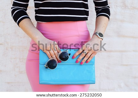 Fashion young woman in pink skirt and black blouse with blue clutch , accessories, watch and sunglasses white background - stock photo