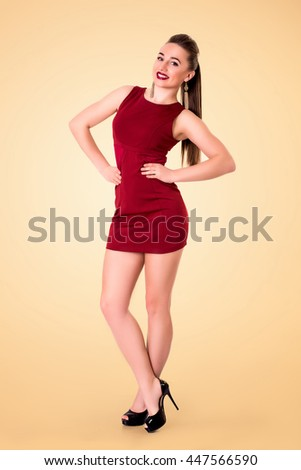 Fashion young  woman posing in short red dress on yellow background - stock photo
