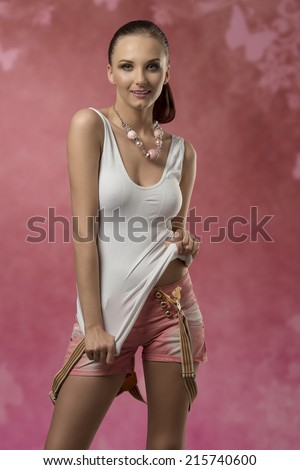 fashion young woman posing with happy expression and smiling, wearing sexy stretch top, shorts and suspenders and yellow wrist watch - stock photo