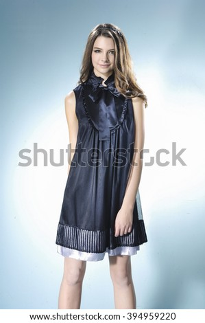 fashion young woman standing-light background - stock photo
