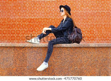 Fashion young woman wearing a black rock style sitting over bricks wall background in profile