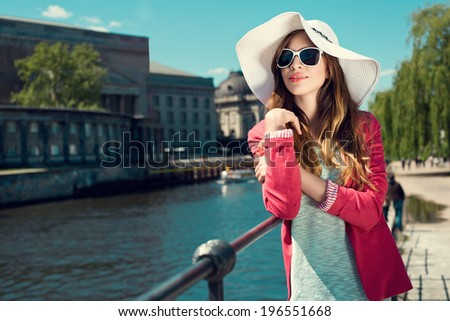 Fashion young woman wearing summer hat and sunglasses at riverside