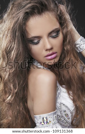 Fashion young woman with curly hair and make up