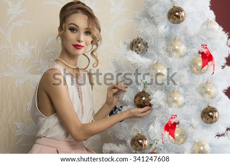 fashion young woman with cute hair-style and elegant dress sitting near decorated christmas tree and looking in camera with happy expression