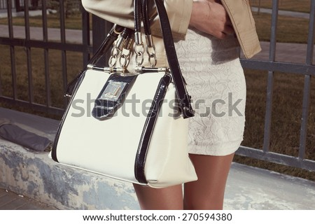 Fashion young woman with handbag and white skirt near street fence closeup, part of the body, instagram color - stock photo