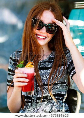 Fashion young woman with long hairs and amazing smile, holding tasty sweet summer cocktail lemonade, elegant dress and ,make up, relaxing at city cafe. happy joyful emotions.