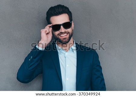 Fashionable and cheerful. Close-up of cheerful young handsome man adjusting his sunglasses and looking at camera with smile while standing against grey background - stock photo