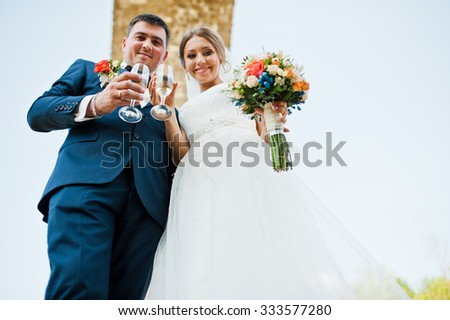 fashionable and happy wedding drinking champagne from glasses under stone bridge