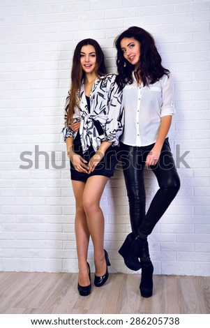 Fashionable and stylish. Young cheerful girls dressed in a black and white and high heels standing  on the  white city wall.