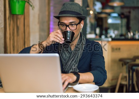 Fashionable and stylish young man drinking coffee, listening music and internet browsing at the cafe bar. Selective focus. Toned image. - stock photo