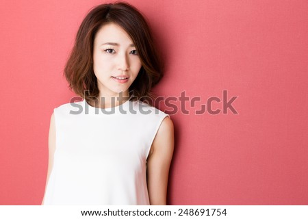 fashionable attractive asian woman isolated on red background