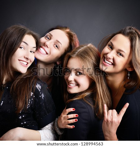 fashionable attractive happy party teen girls smiling over black background