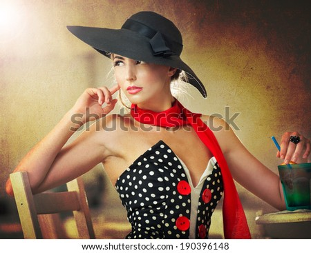 Fashionable attractive lady with black hat and red scarf sitting on chair in restaurant, indoor shot. Young woman posing in elegant scenery. Art photo of elegant sensual woman, vintage style - stock photo