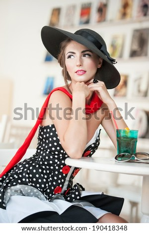 Fashionable attractive lady with black hat and red scarf sitting on chair in restaurant, indoor shot  Young woman posing in elegant scenery  Art photo of elegant sensual woman, vintage style - stock photo