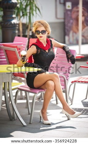 Fashionable attractive lady with little black dress and red scarf sitting on chair in restaurant, outdoor shot in sunny day. Young short hair blonde woman with sunglasses posing having a drink outside - stock photo