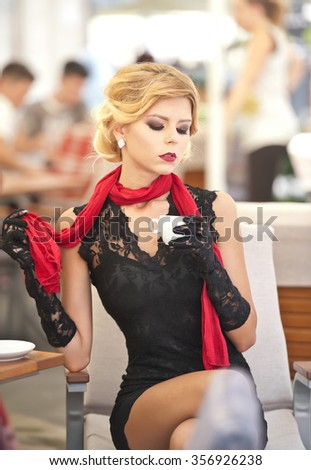 Fashionable attractive lady with little black dress and red scarf sitting on chair in restaurant and drinking coffee. Short hair blonde woman with makeup and creative haircut holding a cup of coffee - stock photo