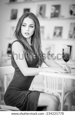 Fashionable attractive young woman in dress sitting in restaurant. Beautiful girl posing in elegant scenery with a juice glass on the table. Pretty female relaxing, indoor shot, black and white photo - stock photo