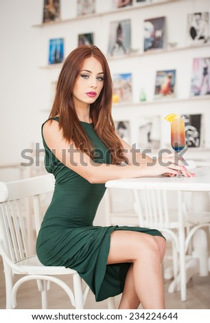 Fashionable attractive young woman in green dress sitting in restaurant. Beautiful redhead posing in elegant scenery with an orange juice glass on the table. Pretty female relaxing, indoor shot.