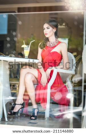 Fashionable attractive young woman in red dress sitting in restaurant, beyond the windows. Beautiful brunette posing in elegant vintage scenery with a lemonade glass. Photo concept through the window - stock photo