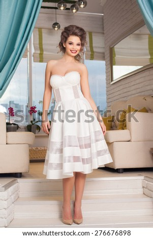 Fashionable attractive young woman in white dress in cafe in Provence style