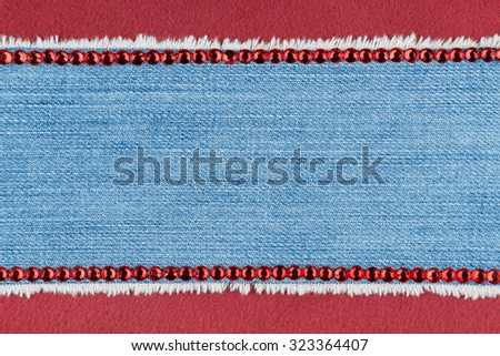 Fashionable background,  jeans and red rhinestones lying on red satin, with space for your text