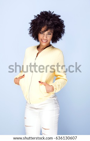 Fashionable beautiful african american woman posing on blue background, smiling.