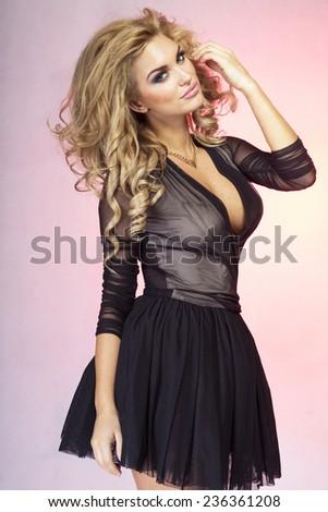 Fashionable beautiful blonde woman posing in studio, wearing dress. Young girl with long healthy hair. - stock photo