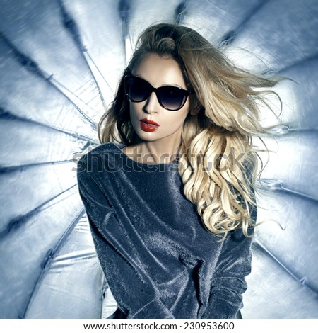 Fashionable beautiful blonde woman posing in sunglasses. Girl with long curly hair.  - stock photo
