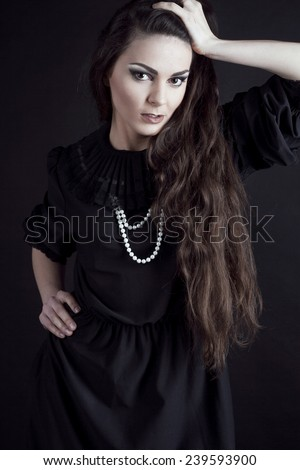 Fashionable beautiful blonde woman with dark lips in black on the studio. Gothic. With long hair. - stock photo