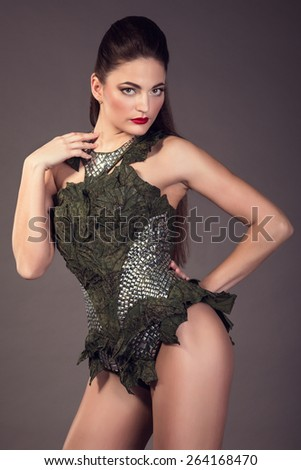 Fashionable beautiful brunette woman posing in studio. The combination of medieval armor and modern military uniforms.  - stock photo