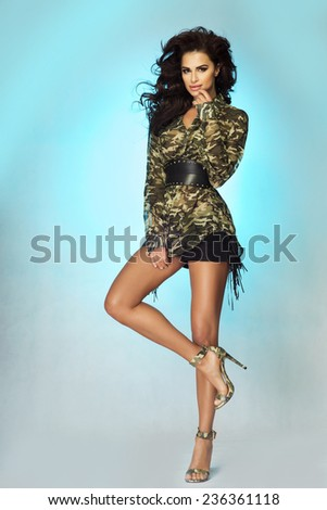Fashionable beautiful brunette woman posing in studio. Young girl with long healthy hair. - stock photo