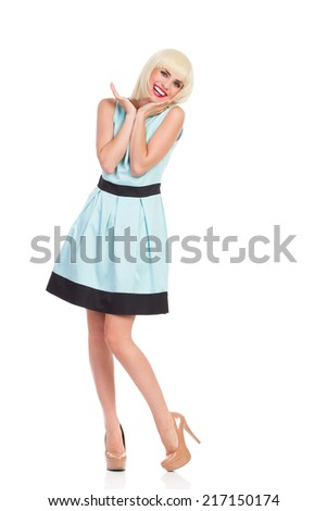 Fashionable beautiful girl posing in pastel blue dress, smiling and holding hand on chin. Full length studio shot isolated on white. - stock photo