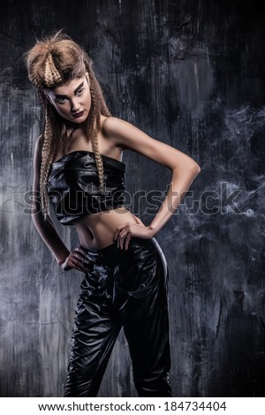 Fashionable beautiful woman stands in the smoke leather clothes. Photo Shooting for glossy magazine