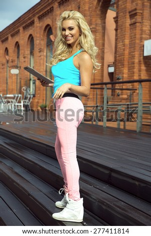 Fashionable beautiful young blonde woman posing outdoor with smile. - stock photo