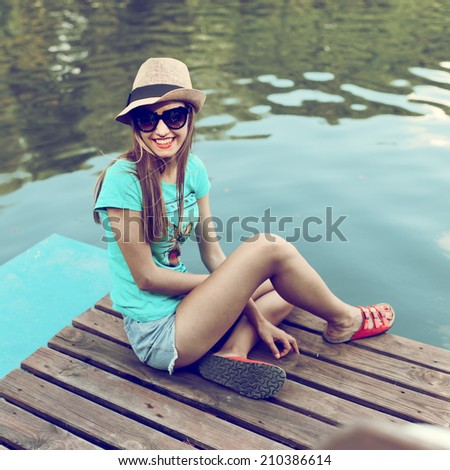 Fashionable beautiful young girl in hat and sunglasses sitting on the boat and laughing - stock photo