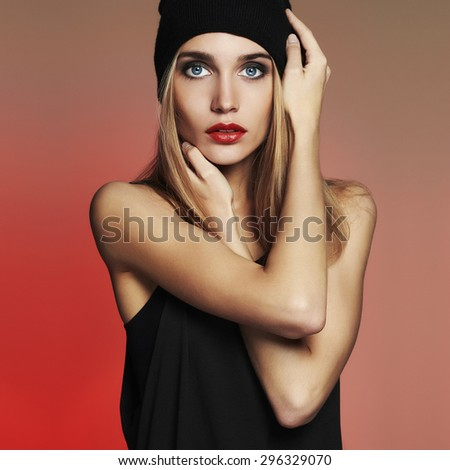 fashionable beautiful young woman in cap. beauty blond girl in hat. red background - stock photo