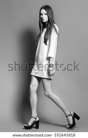 Fashionable beautiful young woman posing in studio, black and white shot - stock photo