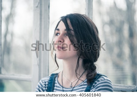 Fashionable beautiful young woman smiling. Dressed in denim overalls. Spring outdoors. Romantic love.
