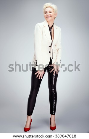 Fashionable blonde adult woman posing in studio, wearing red high heels. Short hairstyle. - stock photo
