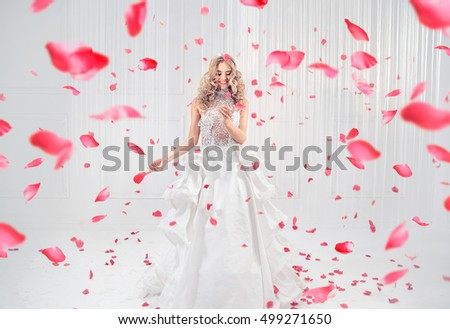 Fashionable blonde beauty among falling rose petals