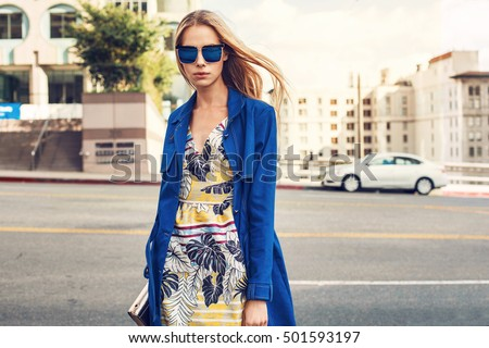 Fashionable blonde woman in jeans coat and nice dress, sunglasses walking in the street. Fashion spring autumn photo