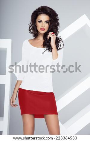 Fashionable brunette beautiful woman posing in elegant style, looking at camera. Studio photo. - stock photo
