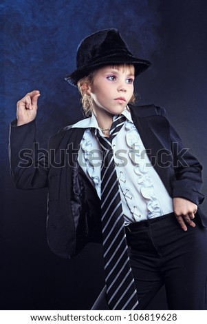 Fashionable brunette girl in a black hat with waving hair posing in studio. Retro style - stock photo