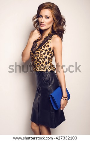 Fashionable brunette model in nice clothes, blue handbag  posing in the studio. Fashion photo